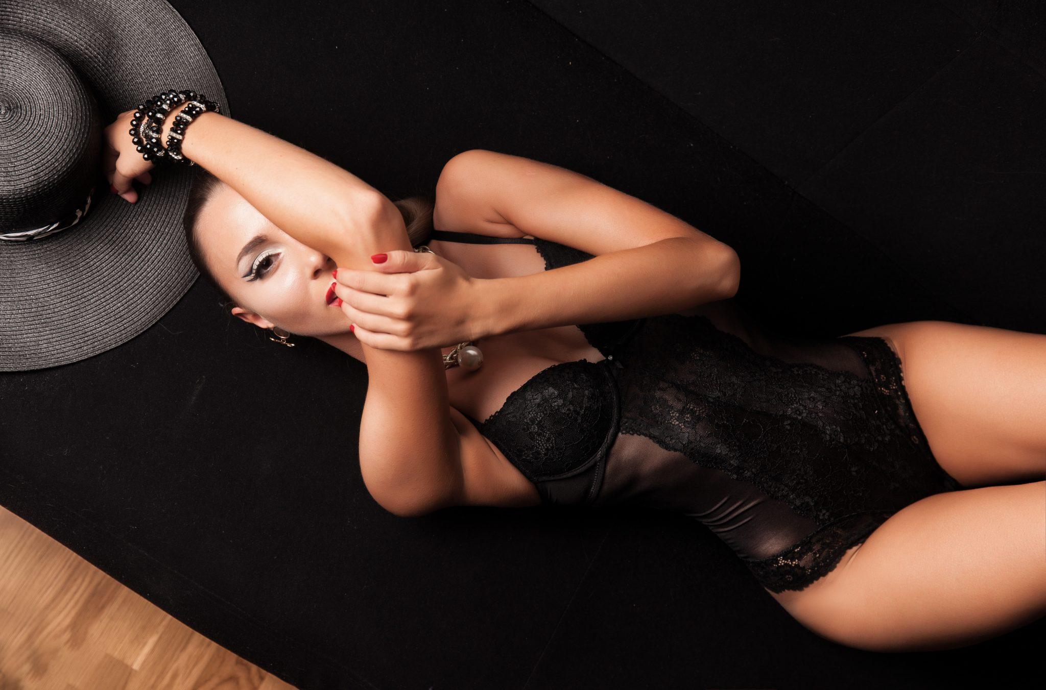 woman in black tank top lying on black textile